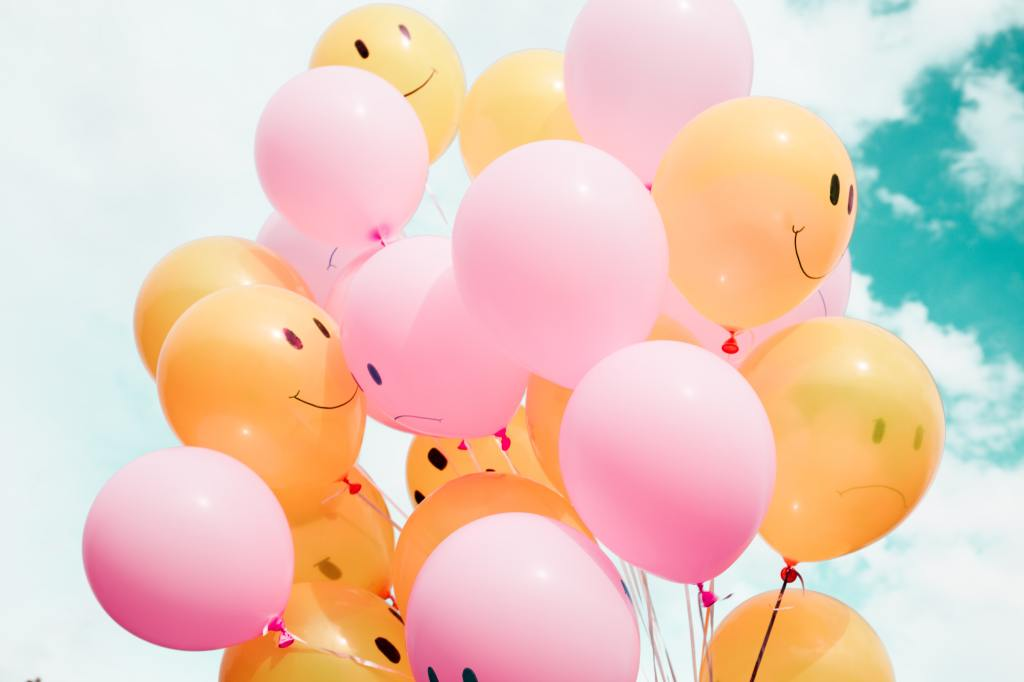 Pink and orange balloons, some with smiley faces painted on