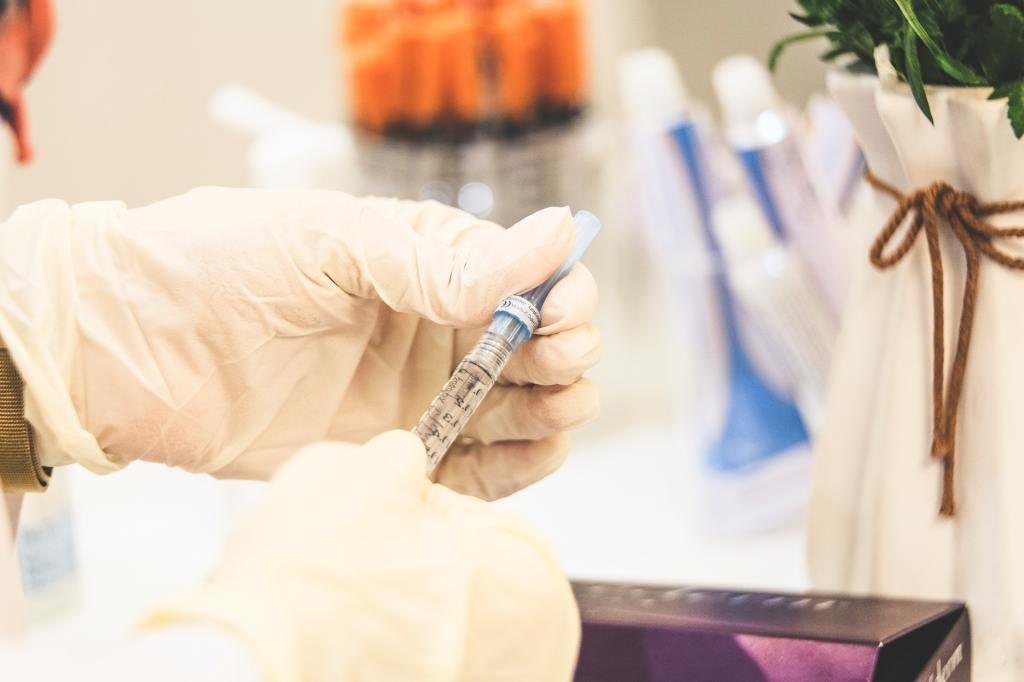 latex gloved hands holding syringe